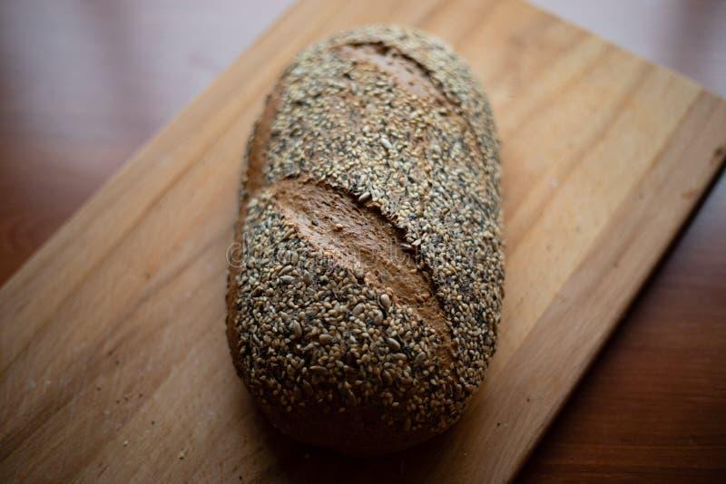 Хлеб Multigrain домодельный на деревянной разделочной доске дома стоковая фотография rf