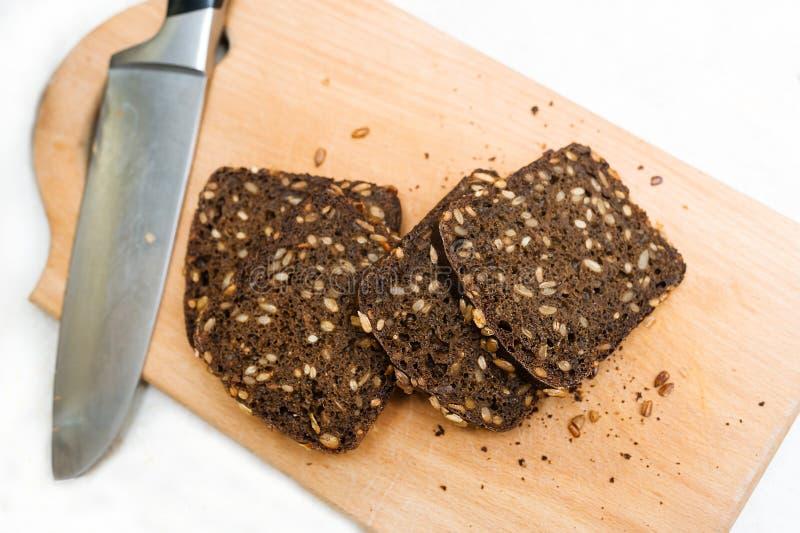 Хлеб Rye с семенами отрезан в части на разделочной доске стоковое фото rf