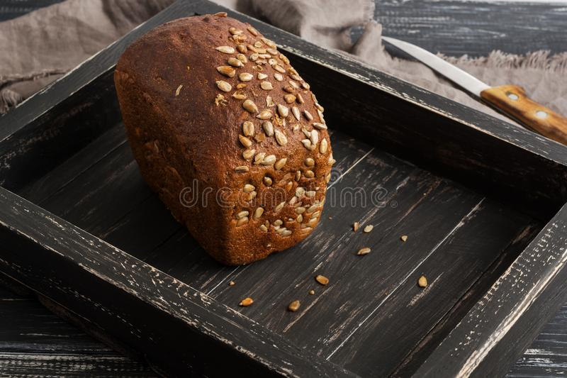 Хлеб Rye с семенами подсолнуха на деревянном черном подносе, салфетке, ноже стоковые фото