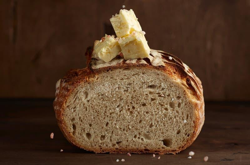 Хлеб sourdough ремесленника с маслом и розовым гималайским солью на темной деревянной предпосылке стоковая фотография rf