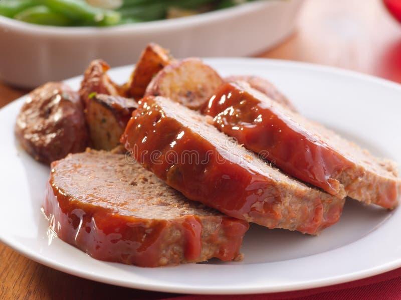 Хлеец мяса с зажаренными в духовке картошками травы стоковые фото