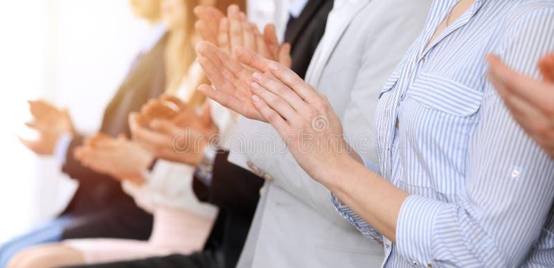 Хлопать и рукоплескание на встрече или конференция бизнесменов, конец-вверх рук Группа в составе неизвестные бизнесмены и стоковые изображения