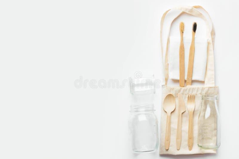 Хлопок, опарник бутылки стекла столового прибора бамбуковых зубных щеток хозяйственной сумки tote ткани ткани деревянный на белой стоковые фотографии rf