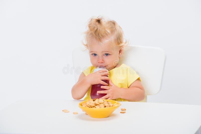 Хлопья хлопьев еды милого маленького ребенка 1 - летние и выпивая сок или компот от бутылки на таблице изолированной на белизне стоковые изображения