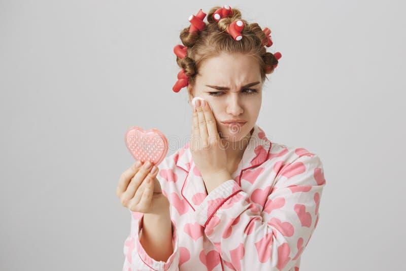 Хмурая докучанная девушка в pyjamas, нося волос-curlers и держать в форме сердц зеркало, обтирающ с состава или туши стоковое изображение rf