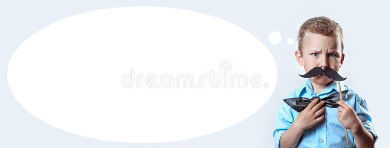 Хмуриться серьезный мальчик в светлой рубашке положил усик на ручку и бабочку на его стороне для того чтобы сделать его выглядеть стоковые фотографии rf