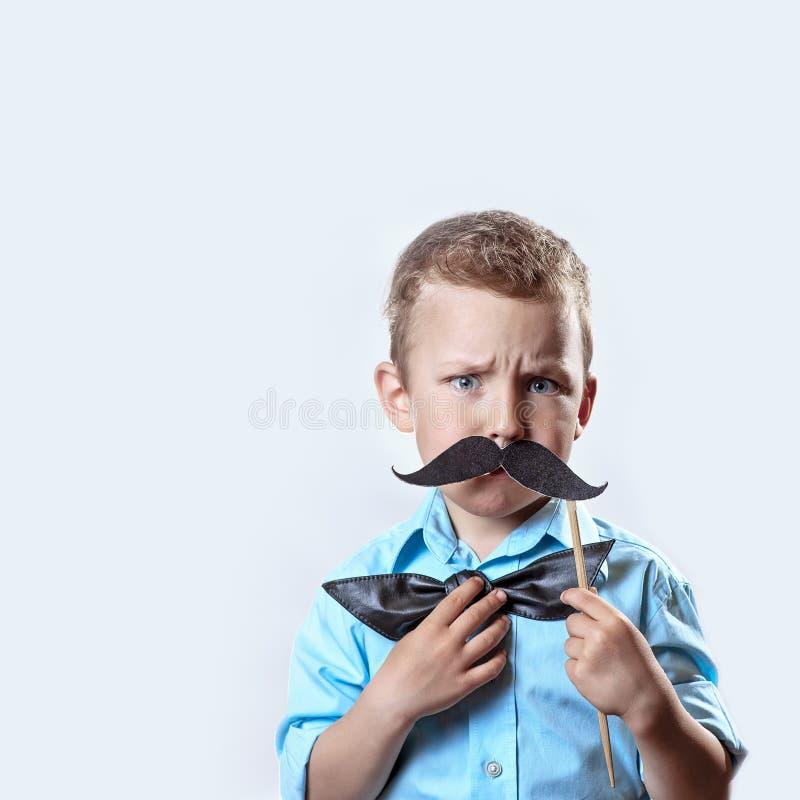 Хмуриться серьезный мальчик в светлой рубашке положил усик на ручку и бабочку на его стороне для того чтобы сделать его выглядеть стоковые фото