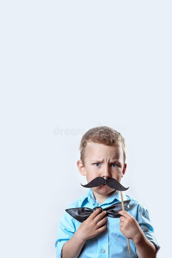 Хмуриться серьезный мальчик в светлой рубашке положил усик на ручку и бабочку на его стороне для того чтобы сделать его выглядеть стоковая фотография rf