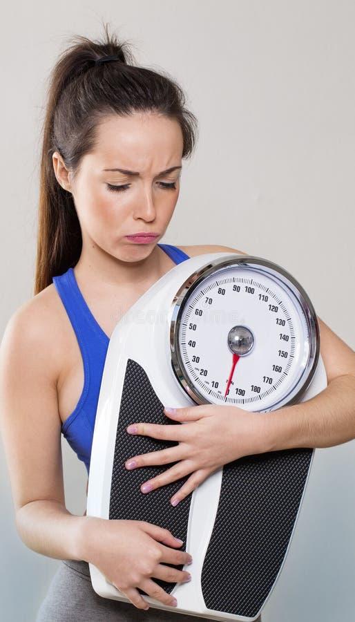 Хмурящся масштабы нося девушки спортзала 20s для проверять потерю веса стоковые фотографии rf