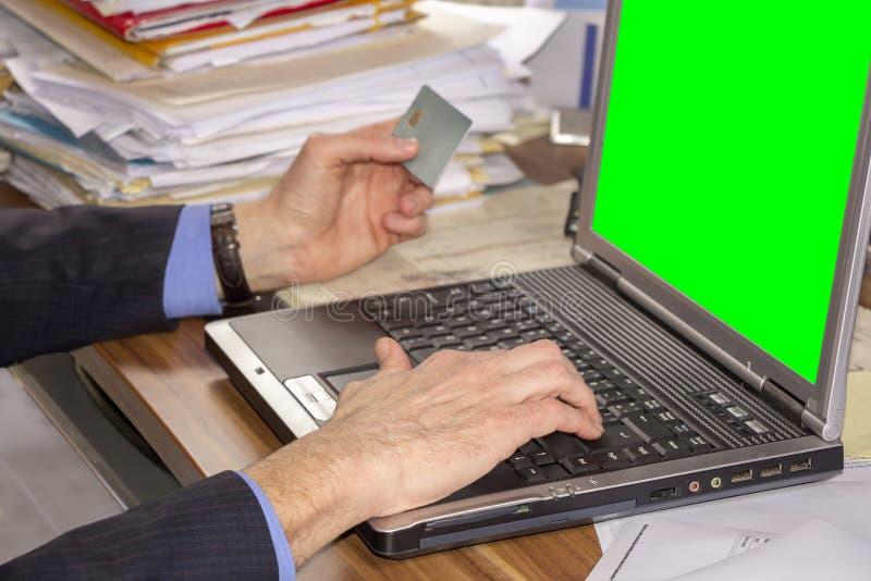 Ходить по магазинам бизнесмена онлайн, используя компьтер-книжку и кредитную карточку стоковая фотография rf