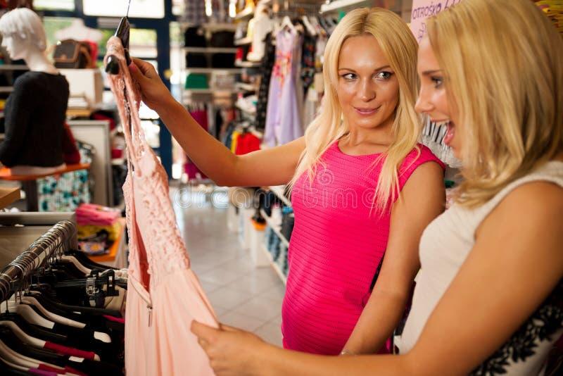 Ходить по магазинам в магазине одежд - 2 милых женщины в магазине одежды выбирают стоковые изображения rf
