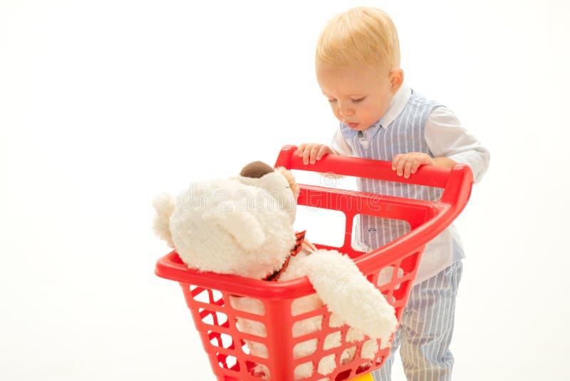 ходить по магазинам для детей сбережения на приобретениях мальчик идет ходить по магазинам с полной тележкой Ребенок мальчика в м стоковые фотографии rf