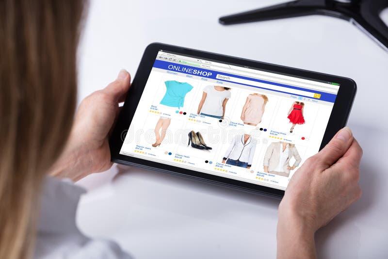 Ходить по магазинам женщины онлайн на таблетке цифров стоковое изображение rf