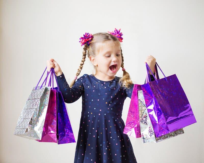 Ходить по магазинам малышей Усмехаясь маленькая девочка с хозяйственными сумками стоковые фотографии rf