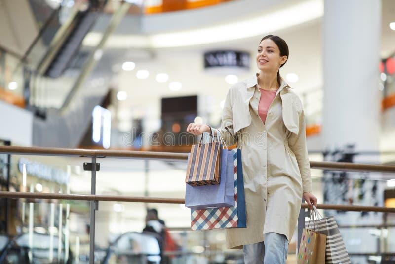 Ходить по магазинам счастливой возбужденной молодой женщины идя стоковое изображение