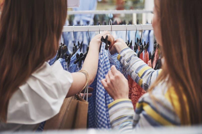 Ходить по магазинам с bestie покупки 2 женщин в магазине розничной торговли Закройте вверх по взгляду стоковое фото