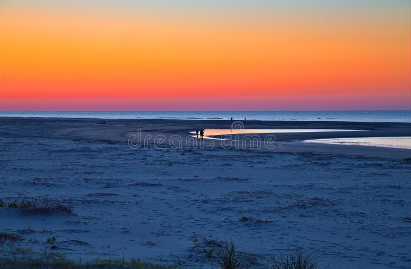 Ходоки на пляже рассвета стоковые изображения rf