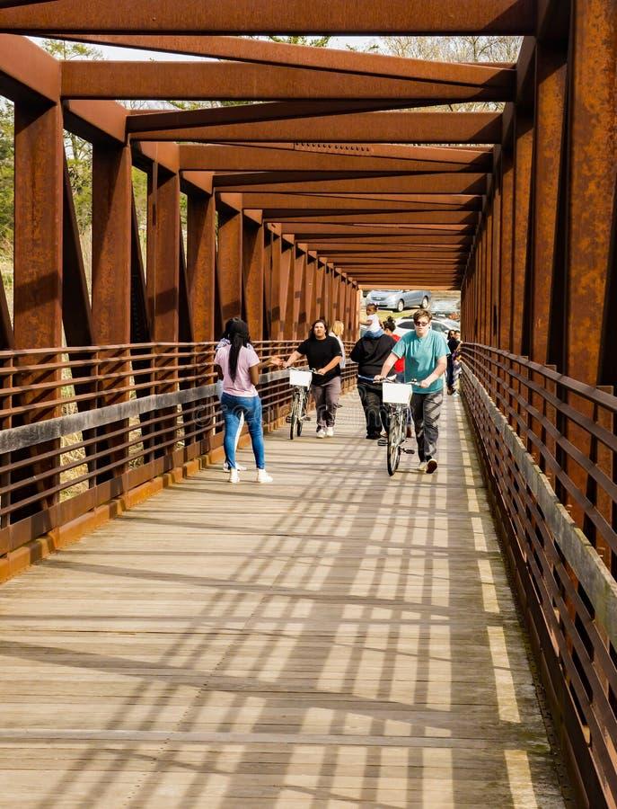 Ходоки пересекая мост металла на Greenway реки Roanoke стоковая фотография rf