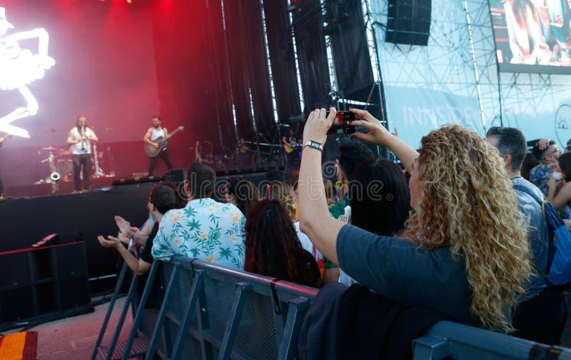 Ходоки фестиваля изображая с их мобильным телефоном шоу на фестивале в реальном маштабе времени mallorca стоковые изображения rf