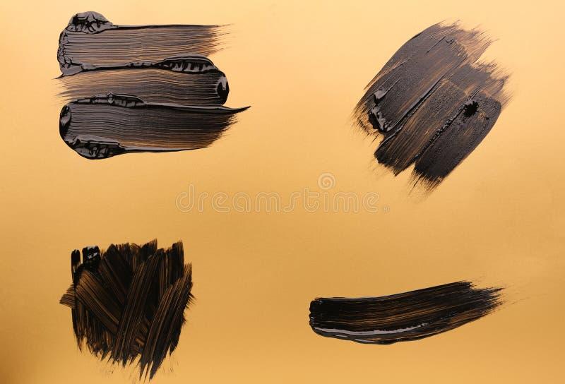 Ходы черной краски на золотой предпосылке стоковое изображение rf