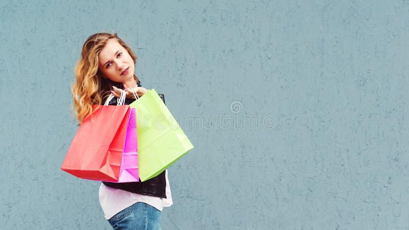 Ходя по магазинам женщина держа хозяйственные сумки цвета Девушка представляя над серой предпосылкой, космосом экземпляра Женские стоковые изображения rf