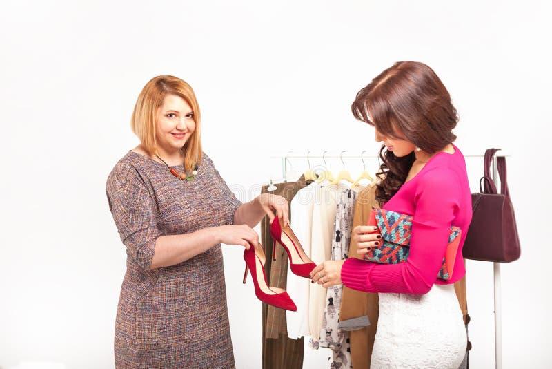 Ходя по магазинам поддержка Красивый стилизатор около шкафа с вешалками стоковая фотография