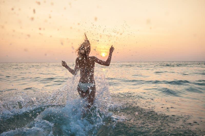 Ход женщины в море с сериями брызгает стоковое изображение