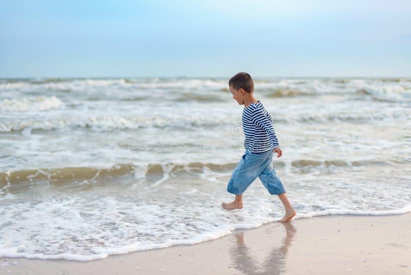 Ход ребенка на пляже r счастливый ребенк играя на пляже на времени захода солнца стоковые изображения rf