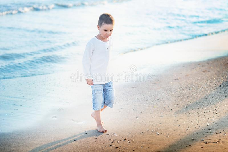 Ход ребенка на пляже r счастливый ребенк играя на пляже на времени захода солнца стоковые изображения