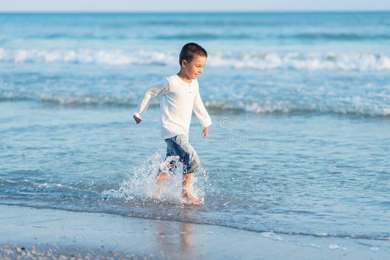 Ход ребенка на пляже r счастливый ребенк играя на пляже на времени захода солнца стоковое фото