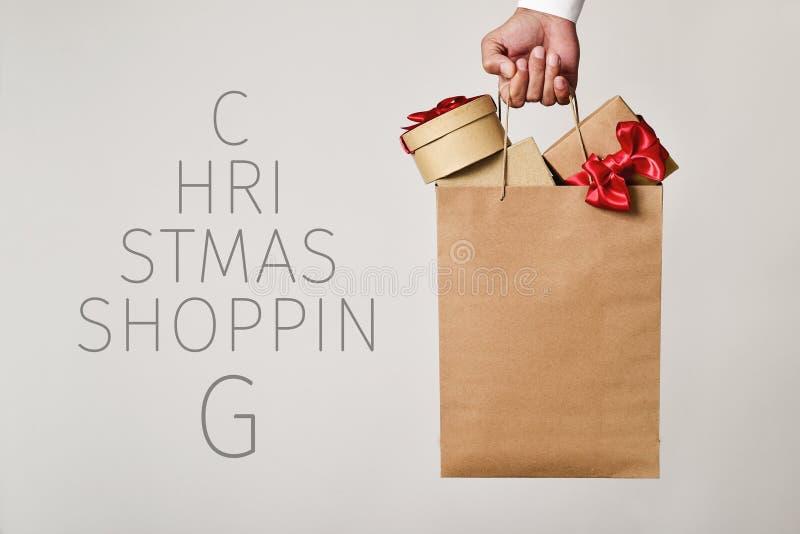 Хозяйственная сумка с подарками и покупками рождества текста стоковые фото