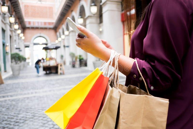 Хозяйственная сумка удерживания женщины и смартфон использования для ходить по магазинам онлайн, ходя по магазинам концепция стоковые изображения rf