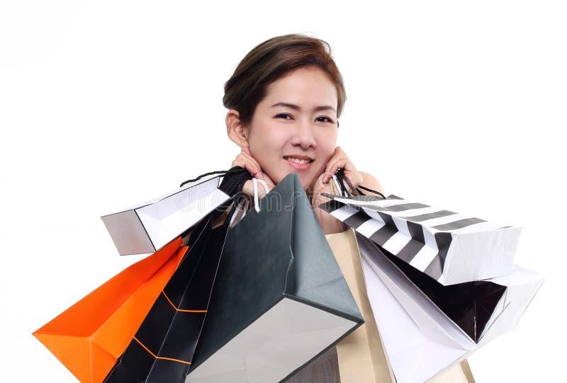 Хозяйственные сумки женщины покупок азиатские счастливые усмехаясь держа изолированные на белой предпосылке стоковое изображение
