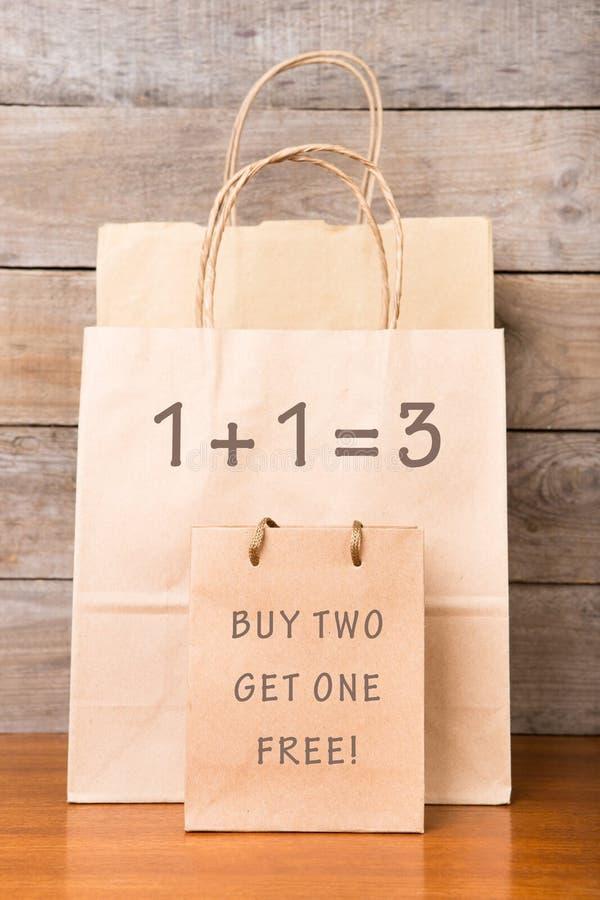 Хозяйственные сумки картона с текстом ' 1+1=3 покупка свободная получает одно 2 стоковые изображения rf
