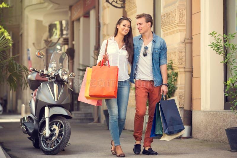 Хозяйственные сумки нося пар на улице города стоковые фотографии rf