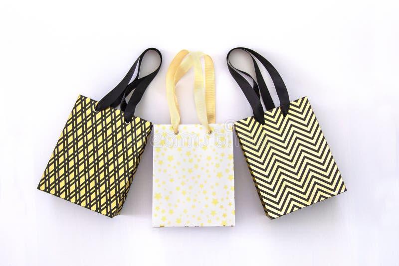 Хозяйственные сумки, подарочные коробки в современном стиле на белой предпосылке Золотые звезды, черные геометрические линии фасо стоковые фото