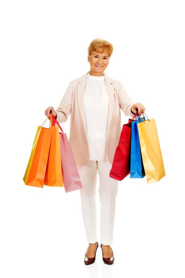 Хозяйственные сумки счастливой бизнес-леди holging стоковое изображение