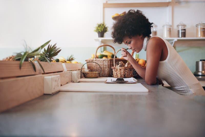 Хозяйчик высчитывать бара сока ее общефирменные расходы стоковое фото