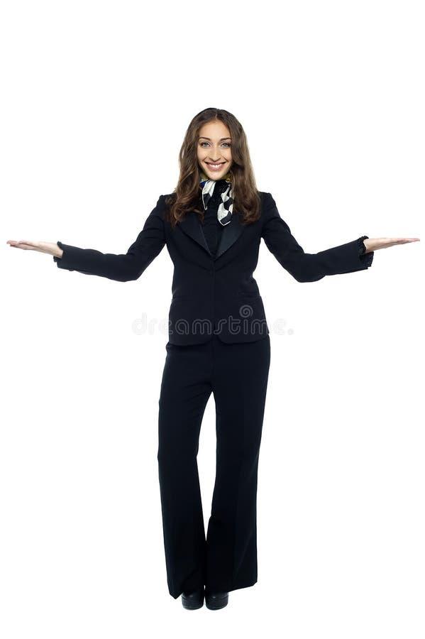Хозяюшка воздуха приветствуя пассажиров стоковое изображение