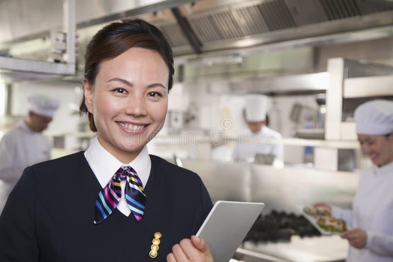 Хозяюшка ресторана в промышленной кухне стоковые изображения