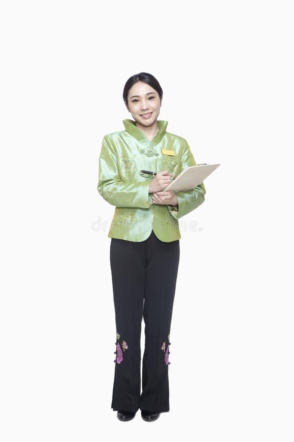 Хозяюшка ресторана/гостиницы в одежде традиционного китайския держа доску сзажимом для бумаги стоковое изображение