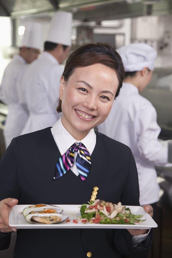 Хозяюшка ресторана представляя тарелку лакомки стоковое изображение