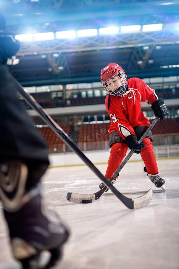 Хоккей на льде игры мальчика в действии пиная на цели стоковые фотографии rf