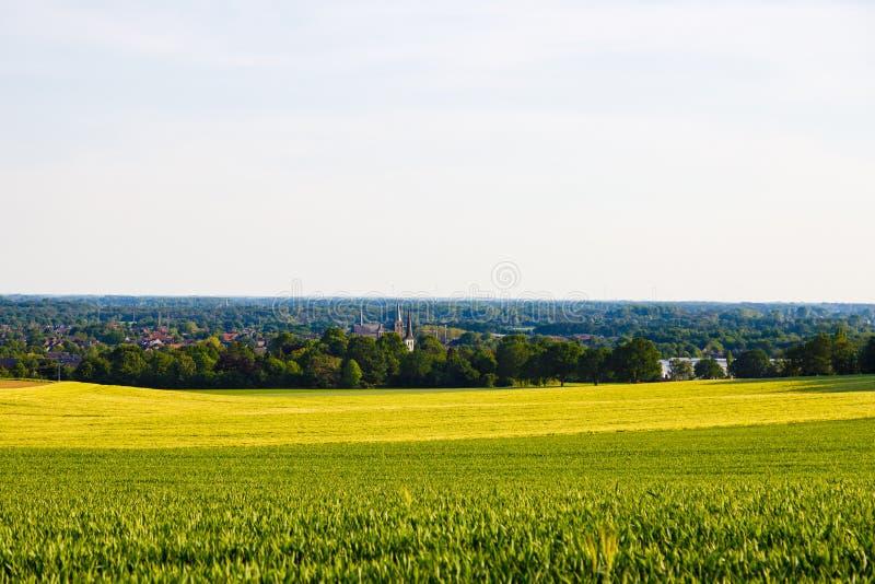 Холмистые сельскохозяйственные угодья в Германии с городскими местностями на заднем плане против голубого и туманного неба caputu стоковые изображения