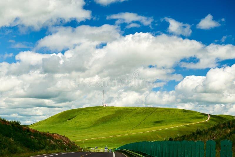 Холм и дорога на злаковике стоковое фото rf