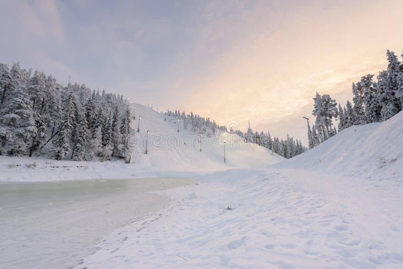 Холм прыжков с трамплина Rukatunturi в сезоне зимы и славное небо погоды и голубых в сезоне зимы и времени захода солнца на лыже  стоковая фотография