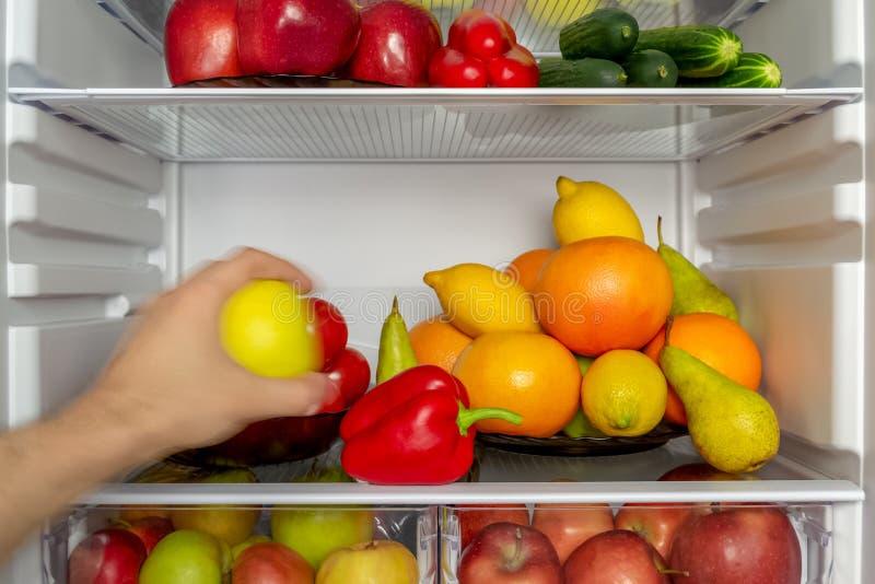 Холодильник заполнен с овощами, плодами Рука принимает еду от холодильника стоковое изображение