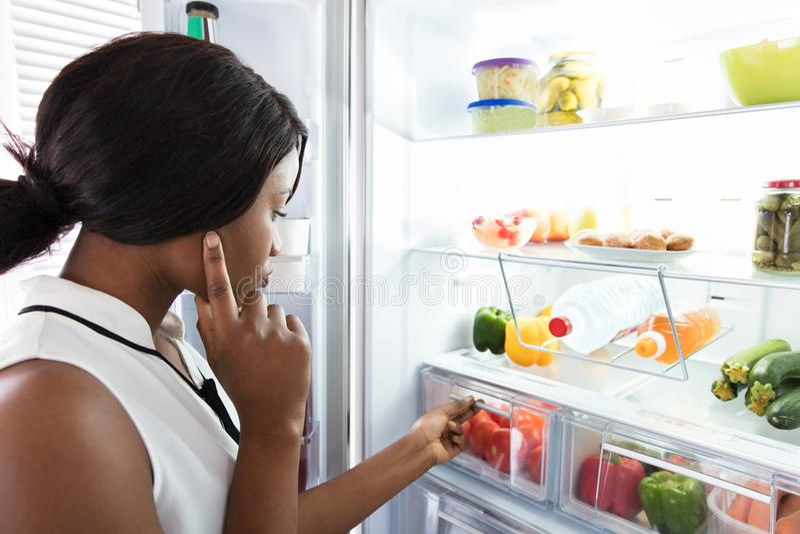 холодильник смотря детенышей женщины стоковые изображения