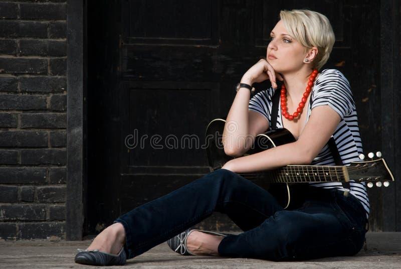 холодная гитара девушки представляя детенышей стоковое фото rf