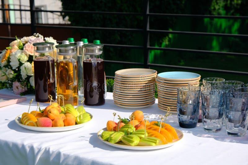 Холодные напитки, соки и вода и отрезали плоды на таблице банкета украшенной букета цветков в ресторане стоковое фото rf